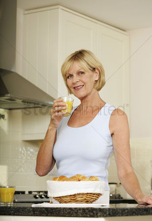 只有成人 : Senior woman holding a glass of orange juice while smiling at the camera