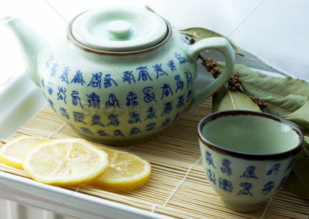 饮料 : Teapot with tea cup and sliced lemons on a tray
