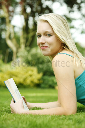 草 : Teenage girl lying forward on the field holding book