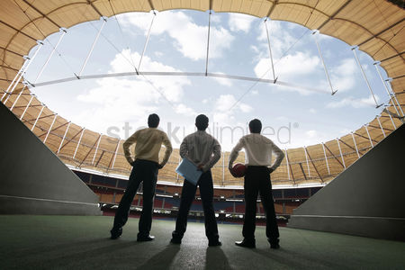 只有成人 : Three businessmen standing at the stadium