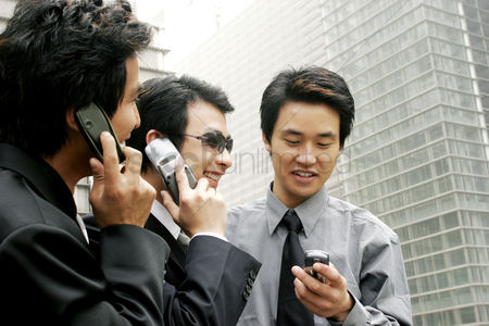 流动性 : Three men in office attires using hand phones
