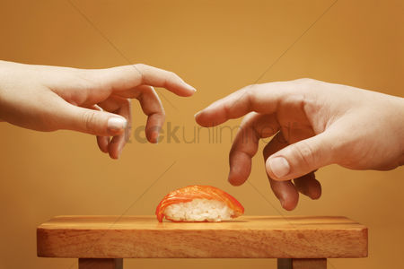 食物 : Two hands trying to take a sushi