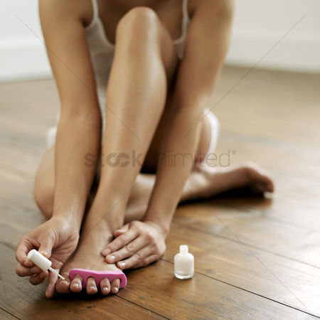 美女时尚 : Woman applying nail polish on her toe nails