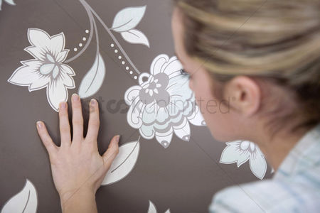内饰 : Woman checking wallpaper s texture