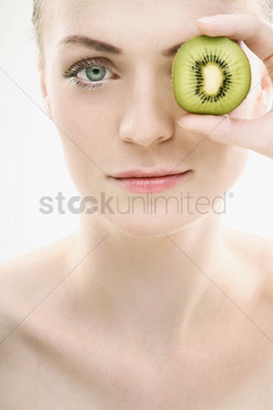 美女时尚 : Woman covering her eye with kiwi fruit