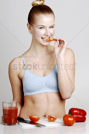 食物 : Woman eating sliced tomato