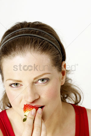 食物 : Woman eating strawberries