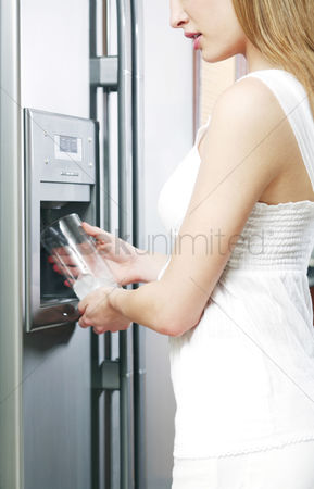 食物 : Woman filling up a glass of water from the refrigerator