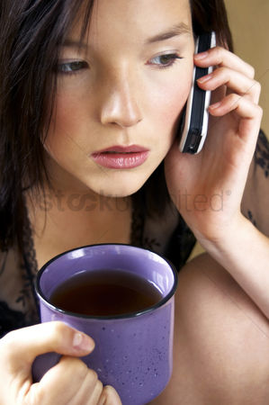 饮料 : Woman holding a cup of coffee while talking on the hand phone
