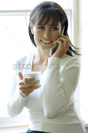 食物 : Woman holding a cup while talking on the phone