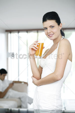 饮料 : Woman holding a glass of orange juice while smiling at the camera