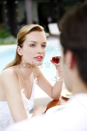 公园户外 : Woman holding a glass of red wine while talking to her boyfriend