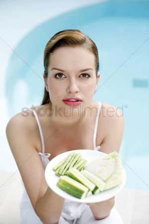 食物 : Woman holding a plate of green vegetables