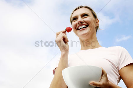 食物 : Woman holding a strawberry and a bowl
