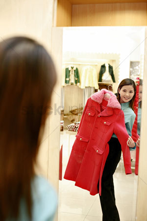 购物 : Woman holding up a coat while looking at the reflection in the mirror