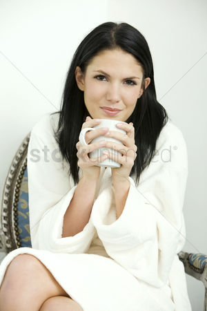 食物 : Woman in bathrobe holding a cup of coffee