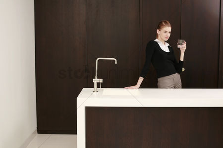 食物 : Woman in formal wear holding a glass of water
