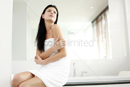 她 : Woman in towel sitting on the bathtub ledge