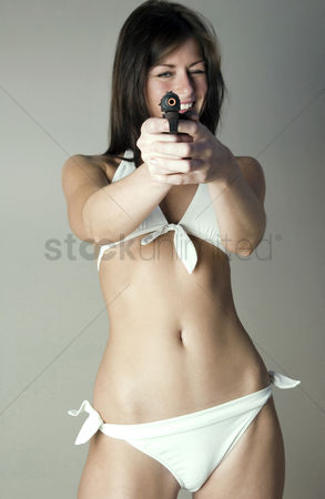 美女时尚 : Woman in white lingerie pointing a gun at the camera