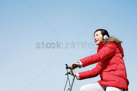 体育 : Woman listening to music while cycling