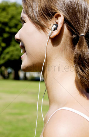公园户外 : Woman listening to music while jogging in the park