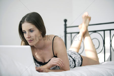 流动性 : Woman lying forward on the bed using laptop