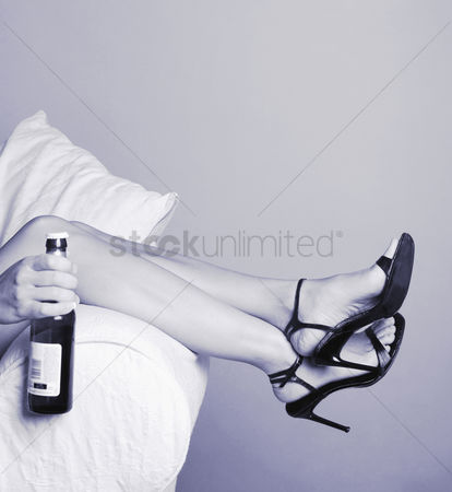 她 : Woman lying on the couch holding a bottle of alcohol