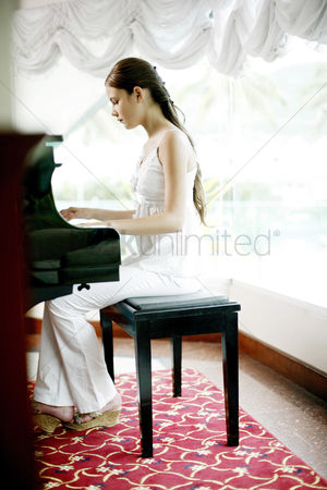 她 : Woman playing piano at home