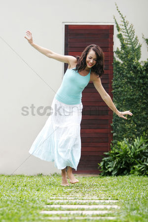 草 : Woman playing with paving stones in a garden