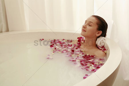 花 : Woman relaxing in bathtub with flower petals