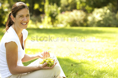 食物 : Woman sitting on the field holding green grapes