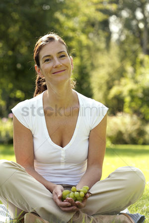 草 : Woman sitting on the field holding green grapes