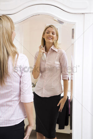 美女时尚 : Woman spraying perfume on her neck while looking at the mirror