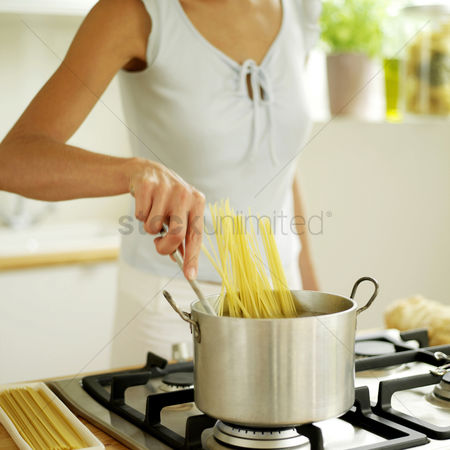 食物 : Woman stirring spaghetti in pot