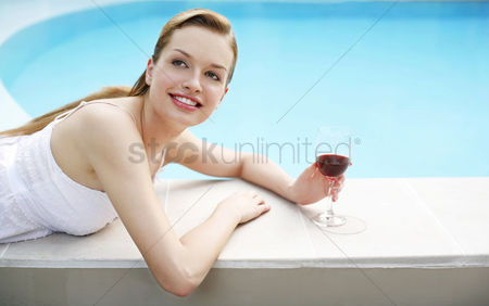 食物 : Woman with a glass of red wine relaxing on the pool side