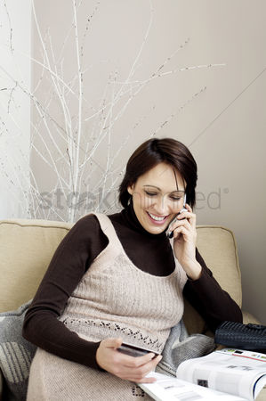购物 : Woman with credit card talking on the phone while reading magazine