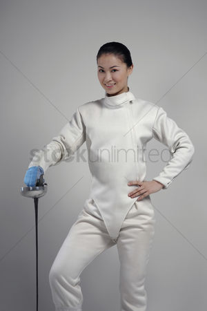 体育 : Woman with fencing foil posing for the camera