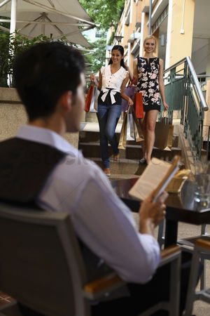 购物 : Women with shopping bags walking down the stairs  man reading book in an outdoor cafe