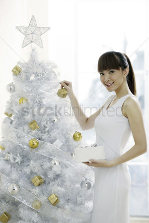 她 : Young woman decorating christmas tree